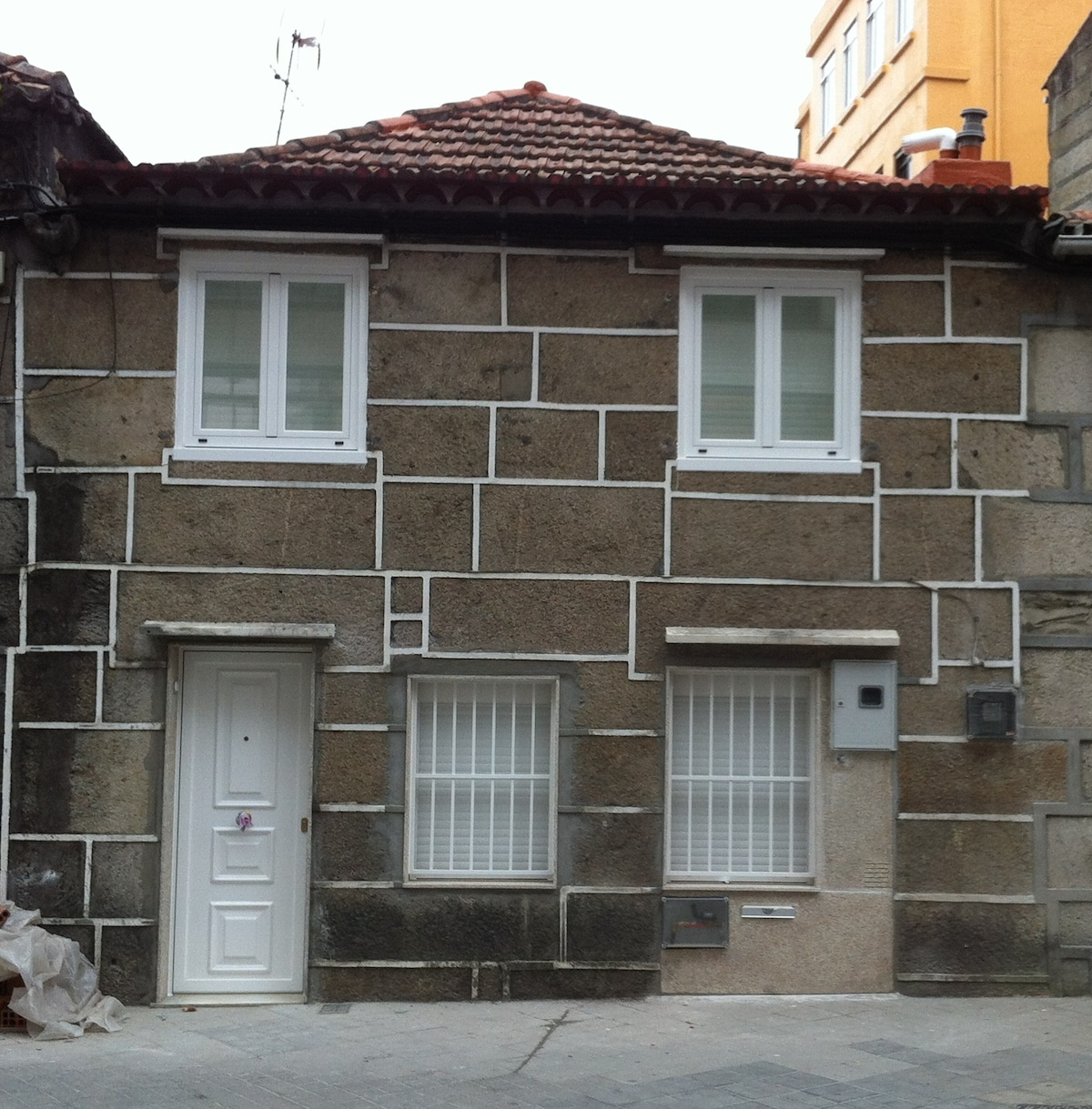 Stone facade with white aluminium door and windows. Casa de piedra original.