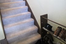 Stairs go up to second floor and shoes rack for your shoes