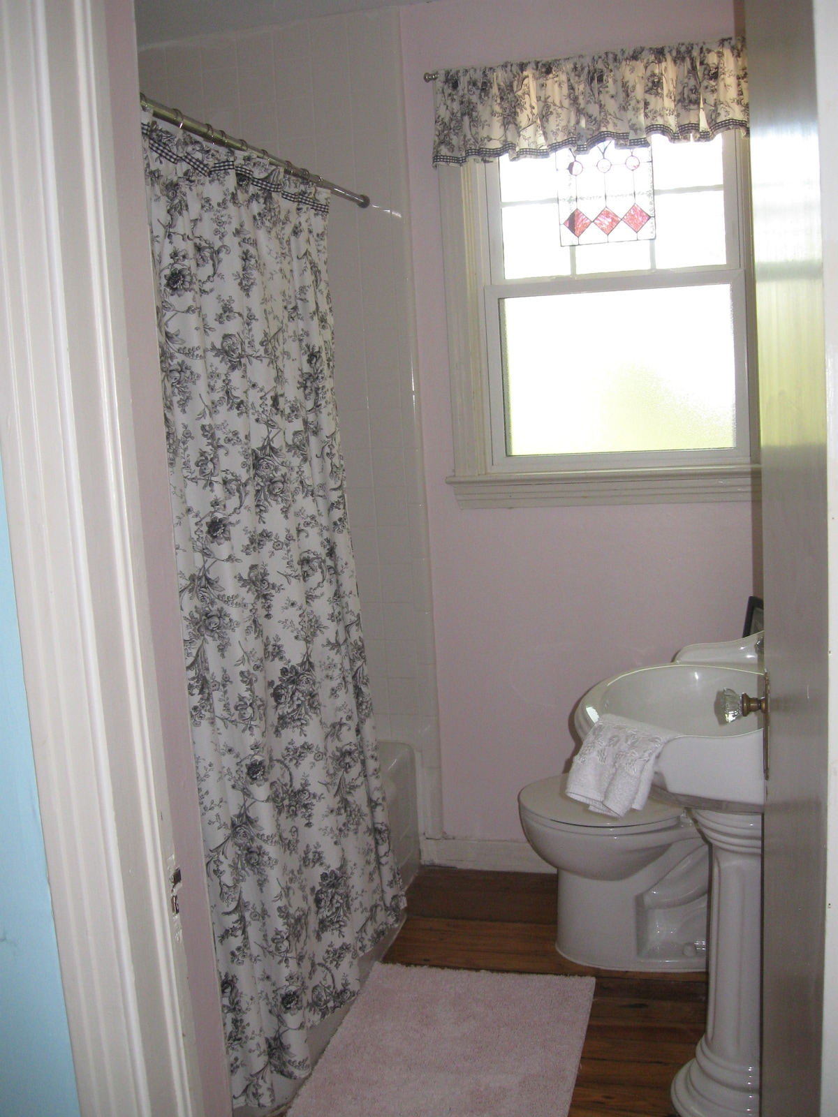 Bathroom with tub/shower and pedestal sink.