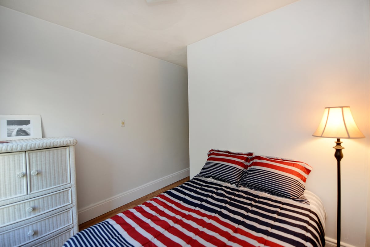 The bedroom is furnished by a full-size bed.