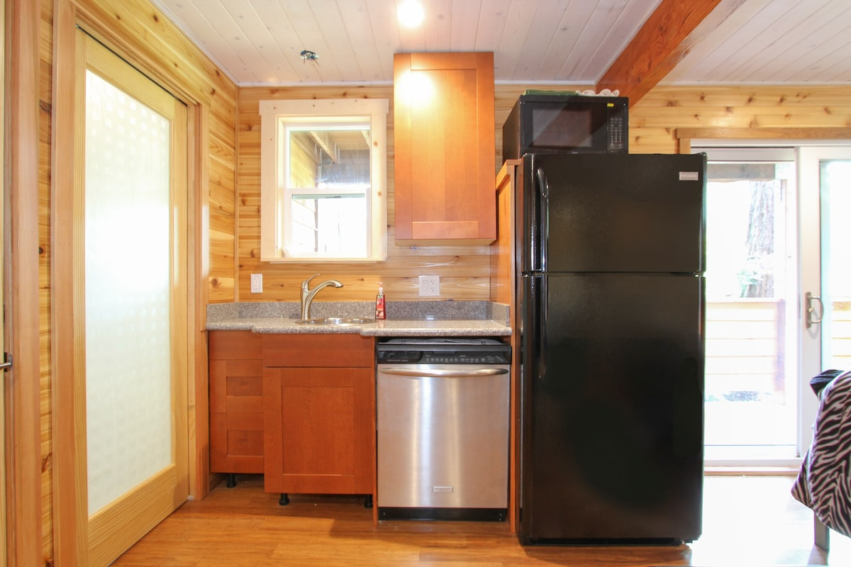 Bright efficiency-kitchenette with wine-speckled granite, Ikea burnt sugar cabinets, new refrig, and plenty of river views!  Cool privacy pocket doors to bath & the 2 bedrooms off the cedar-walled living area with high ceilings