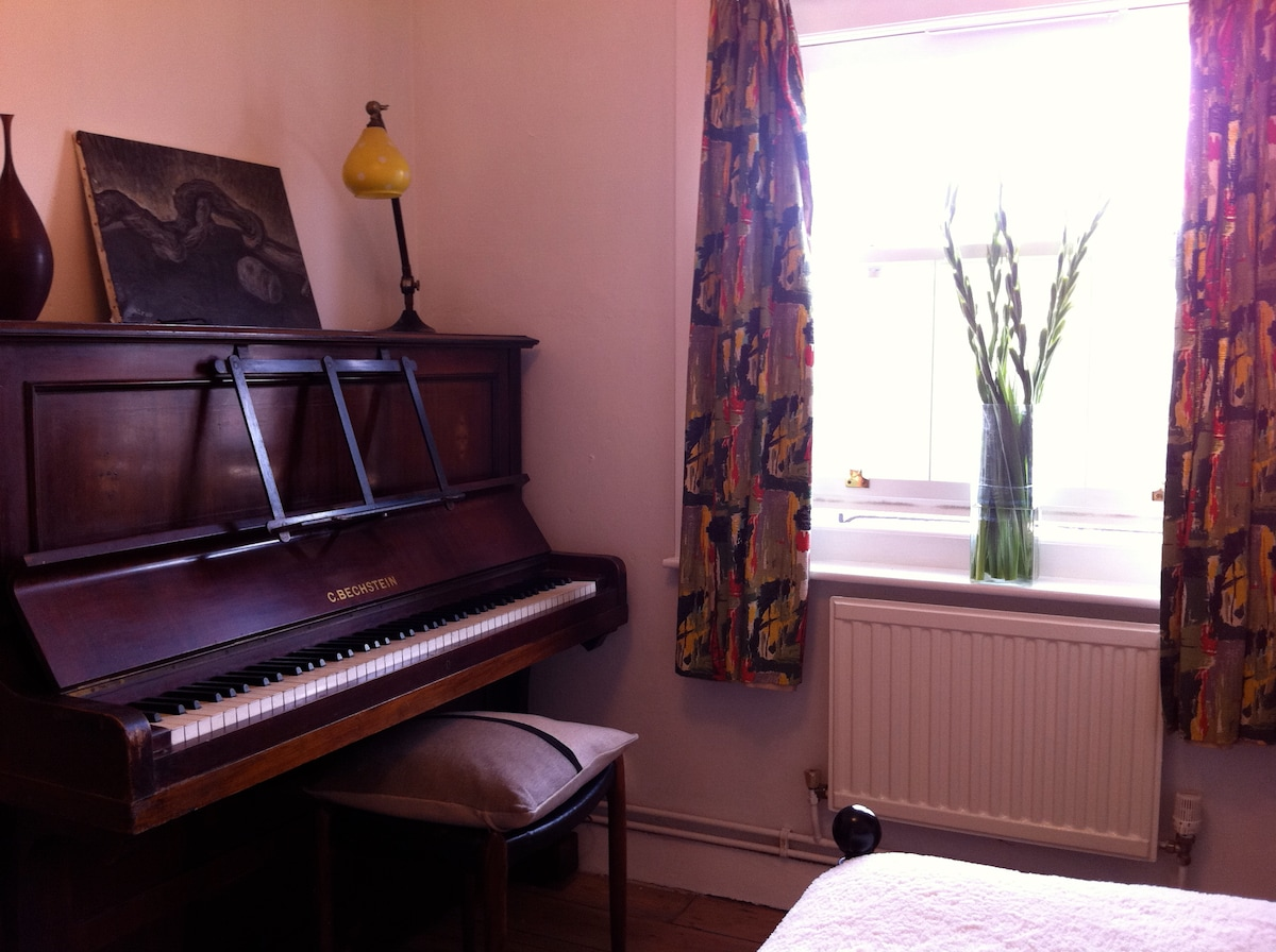 Piano and window from the bed. There's also hanging and storage space.