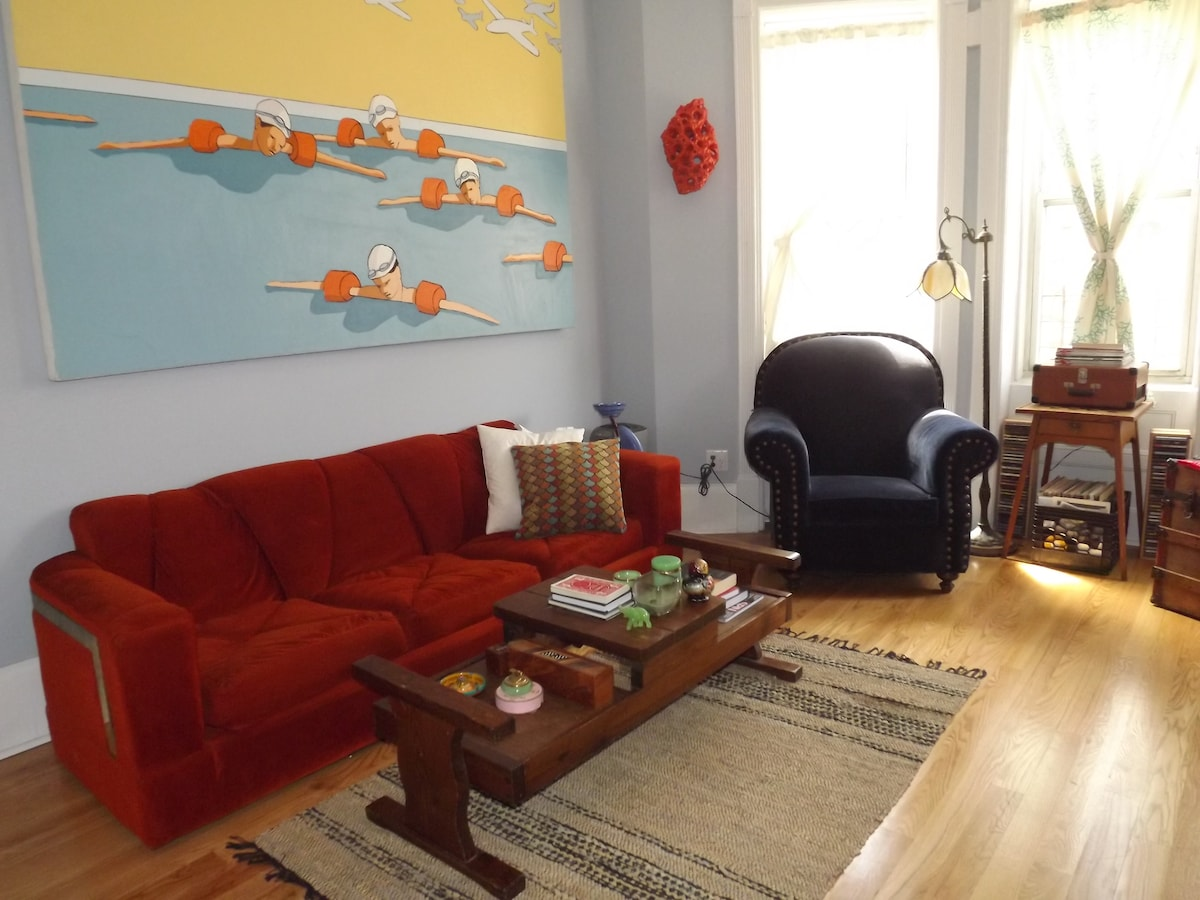 Living room, complete with record player, vintage furniture and art.