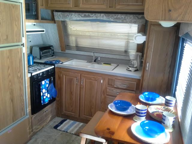 Open kitchen area with large sink, fridge,gas stove coffee maker and lots of storage