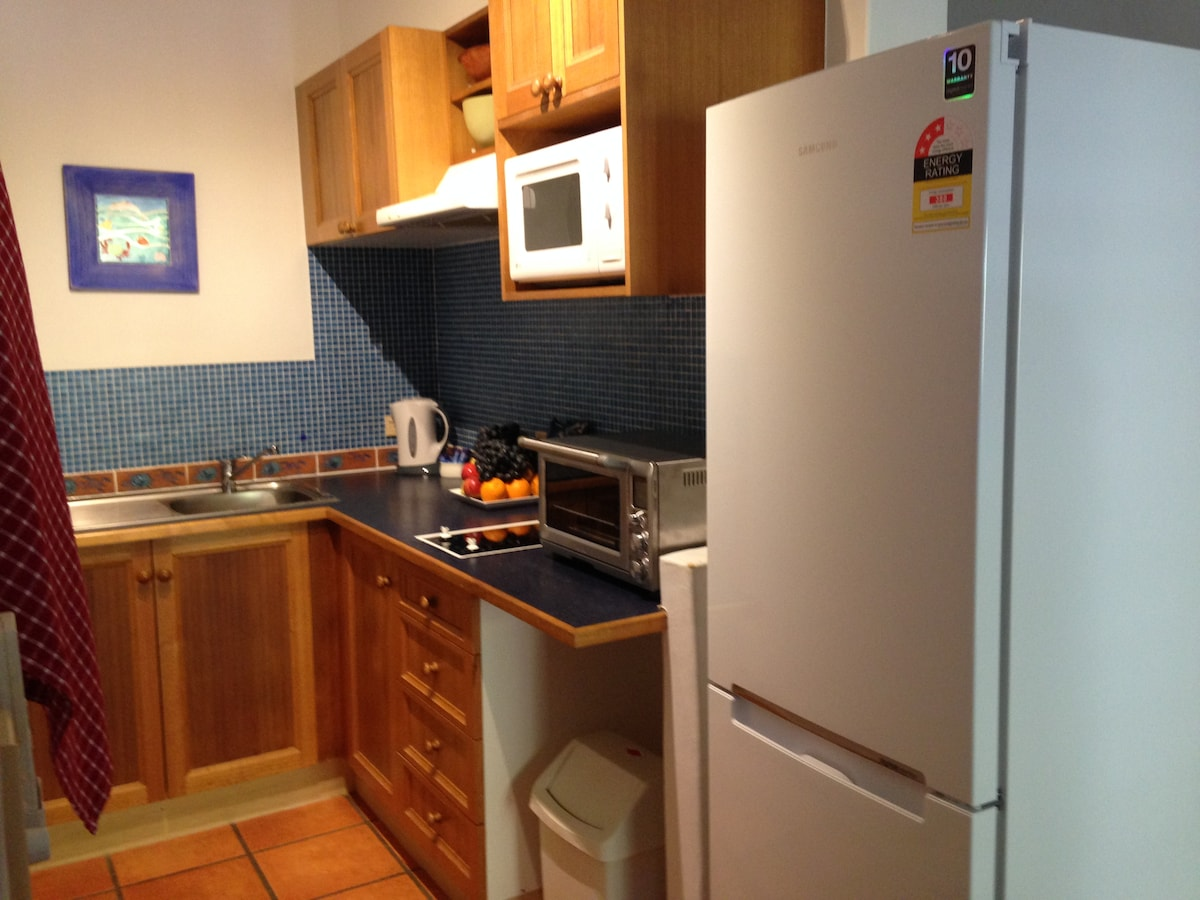Galley kitchen features full-sized fridge, two hot plates, microwave and a separate oven.