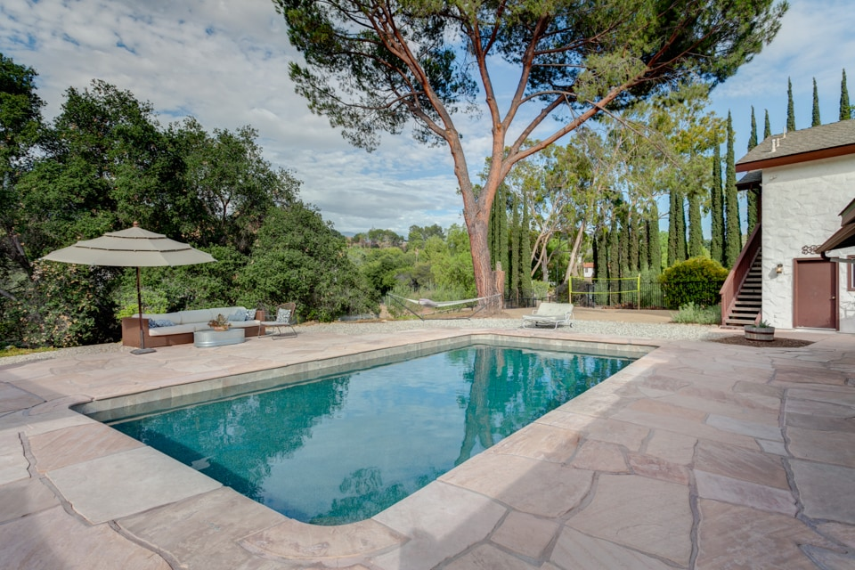 This is the newly redone pebble tech Seasonal pool located next to the outdoor kitchen  and pathway to outdoor shower.