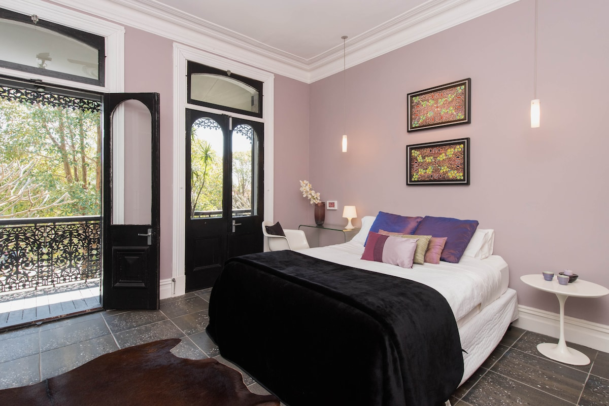 Soft pastels, Aboriginal art, open fire, French doors to the balcony over Johnston Street.
