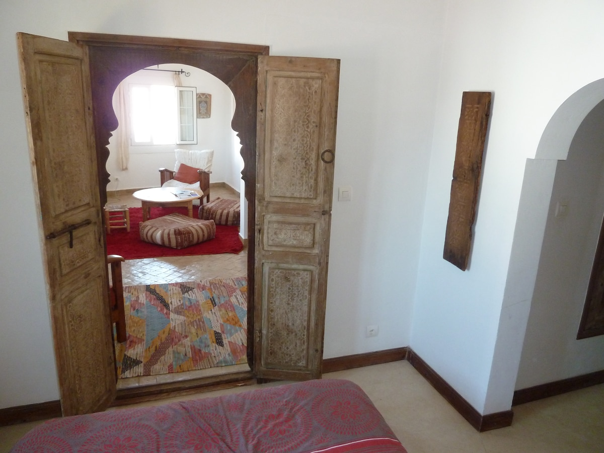 View of the living room, from the Sheherazade master bedroom, with the old carved cedar doors wide open...