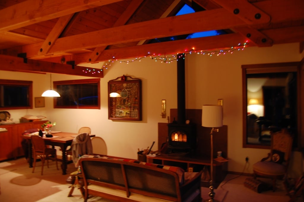 The living/dining area at night, with a cozy fire in the stove.