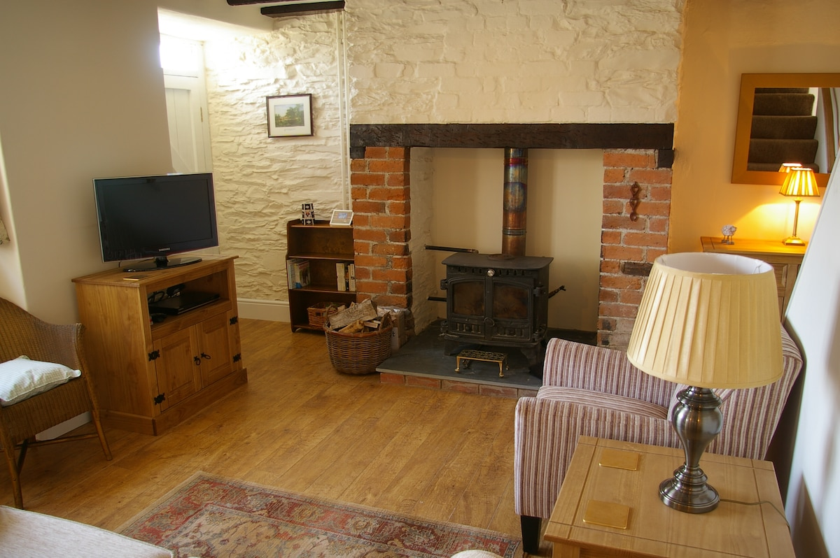 Wood burning stove, TV/DVD and seating in the living room area.