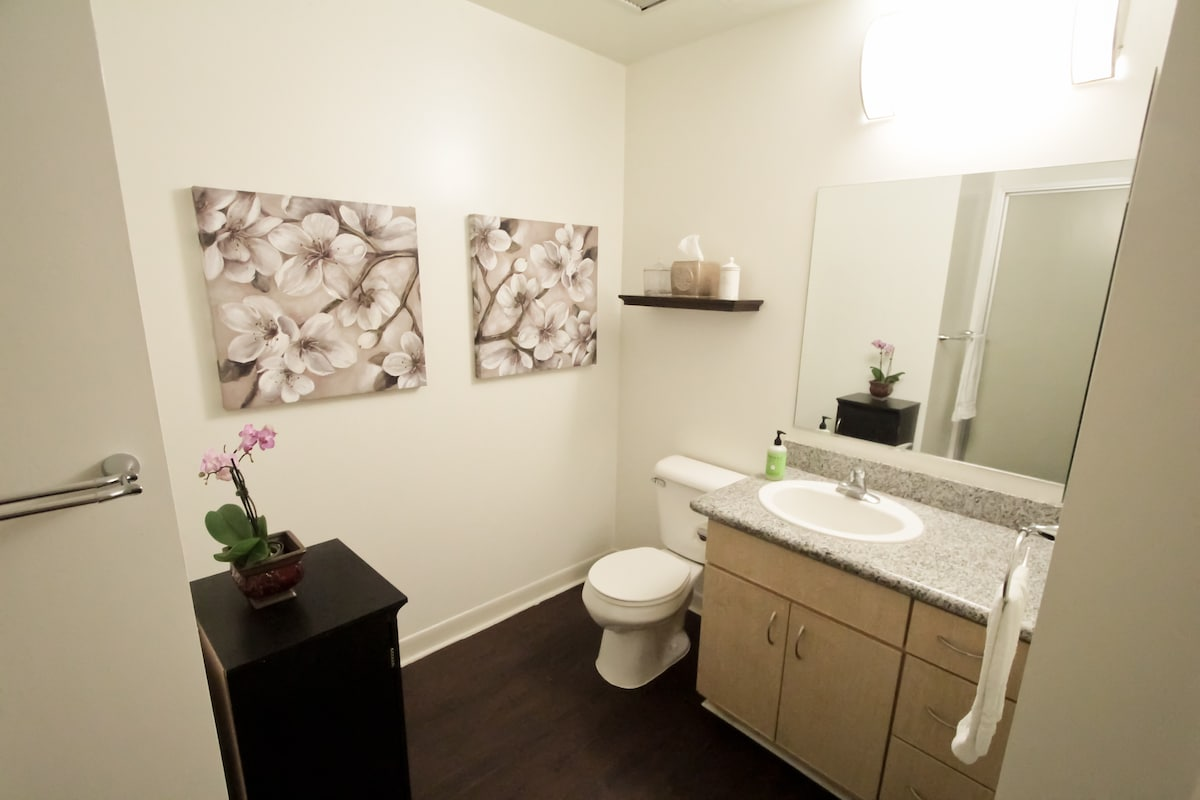Spacious bathroom with clean towels, toiletries, and hair dryer.