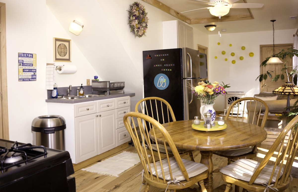 Kitchen area with dining table, sink and side of refrigerator.