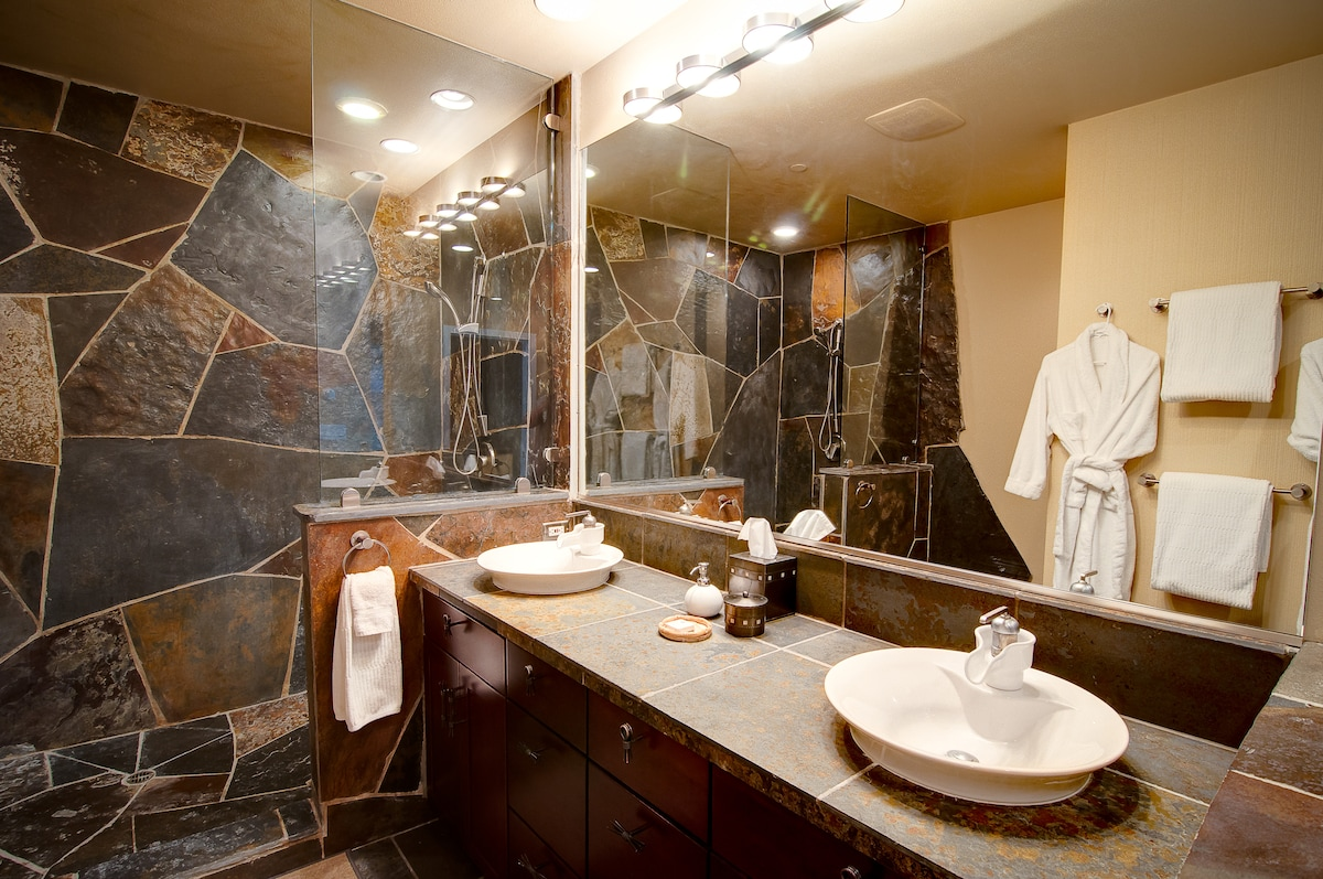 Master bathroom with double sink vanity and dual-shower head rock and glass shower