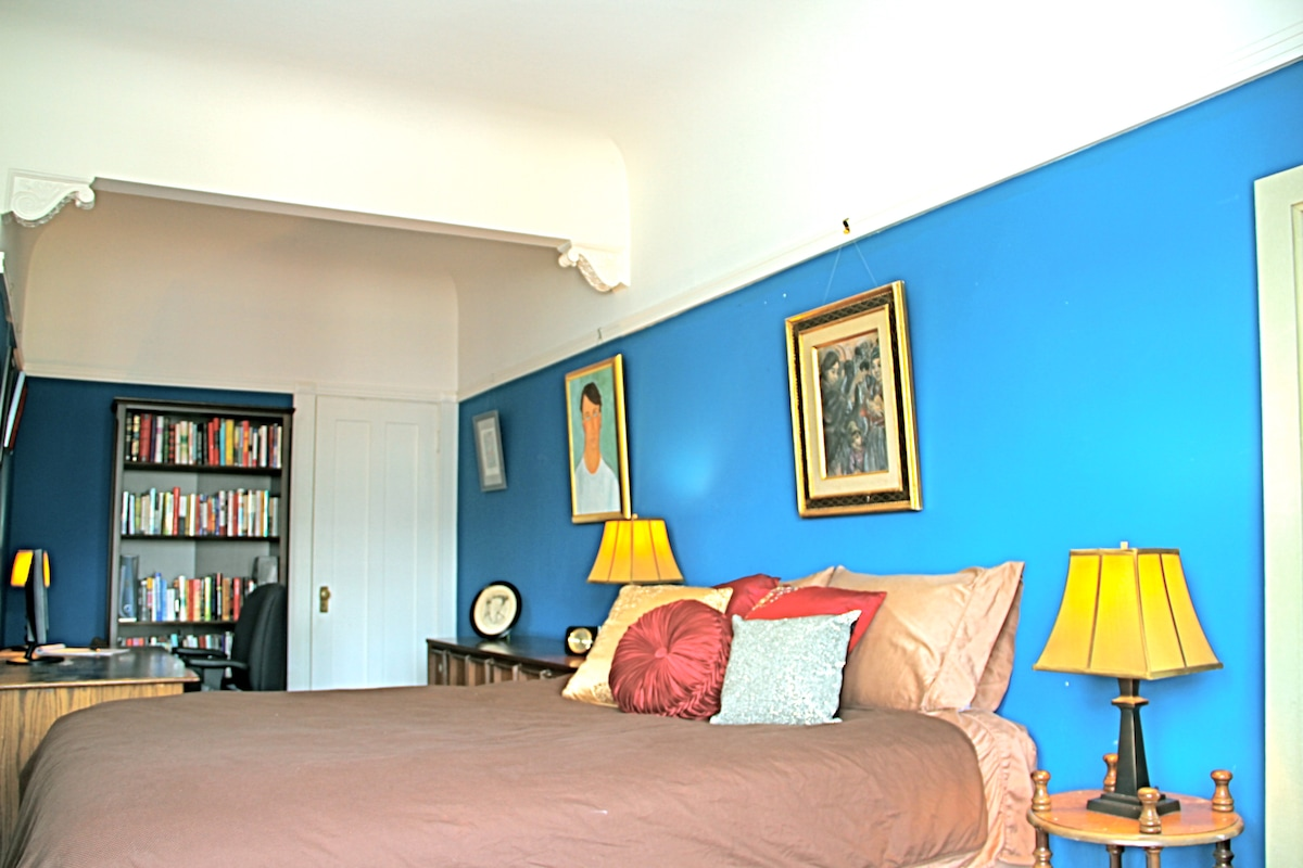 The spacious room includes a workspace nook, queen bed and sitting area.