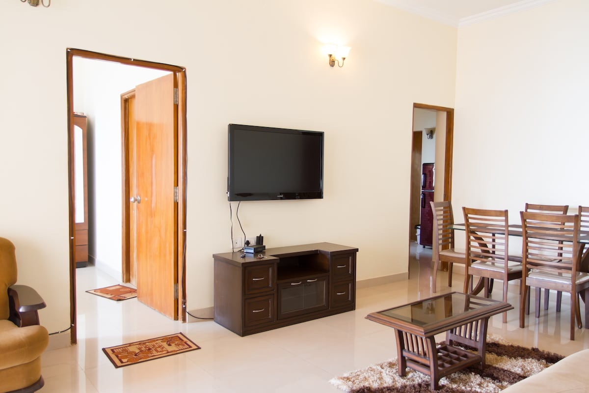 Living room with Dining area, TV. This has a balcony with sea view. Door on left opens into Master bedroom. This Master bedroom has the same sea view. Door on right of the pic is the kitchen entrance.