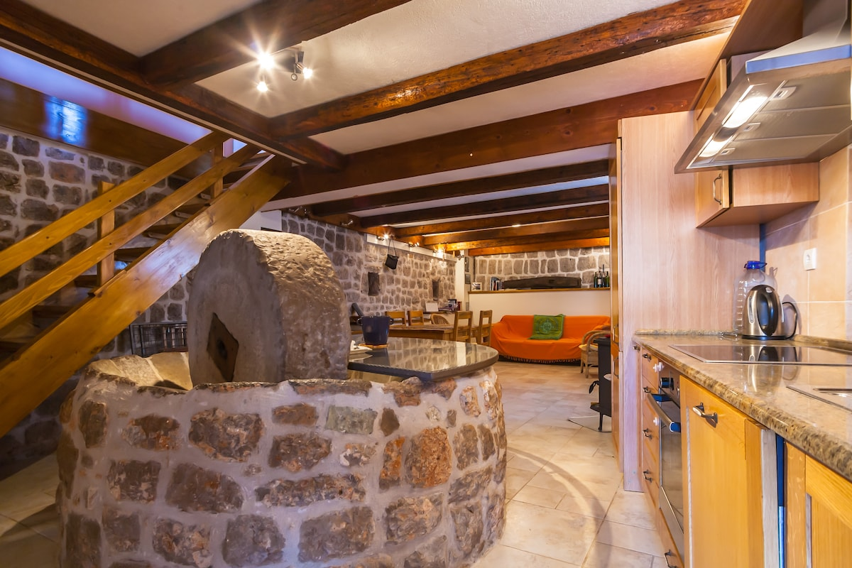But getting back to the house, Let's start inside. Here' s the famous old stone mill and wheel. The room was once used to ground olives -grown on the peninsula- and now forms a feature in the kitchen and lower dining room.