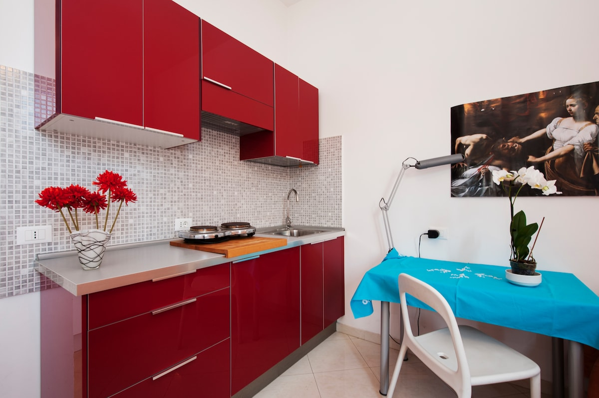 Angolo cottura completo di attrezzature per cucinare e conservare, biancheria da tavola  e spazio pranzo.