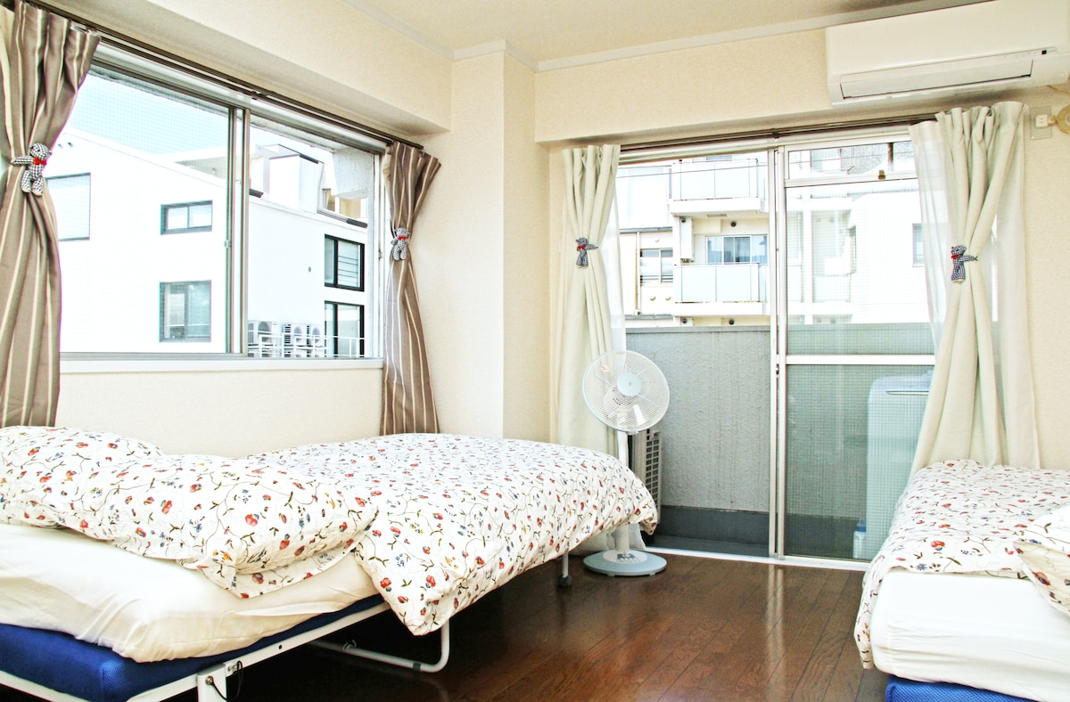 Sunny bedroom with big windows. You can see lovely park and nice view from outside these windows
