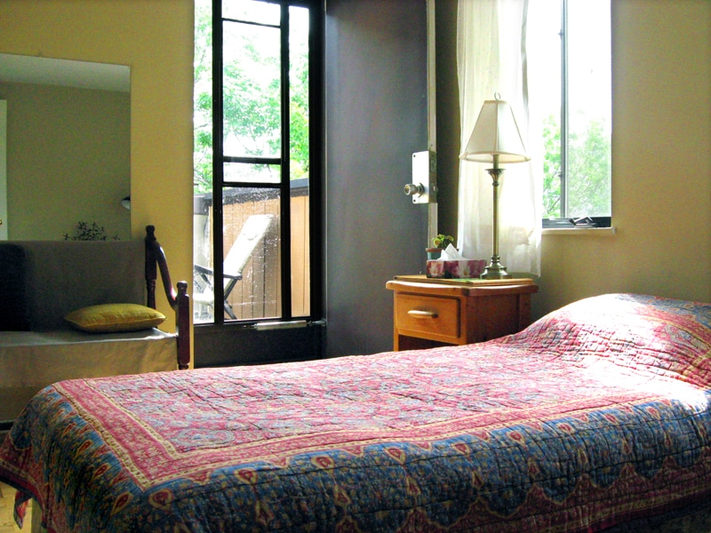 The room with door opening onto a south-facing balcony with bright morning light. The windows overlook a tree-lined residential street. Comfortable all-cotton futon bed wth hypo-allergenic bedding.