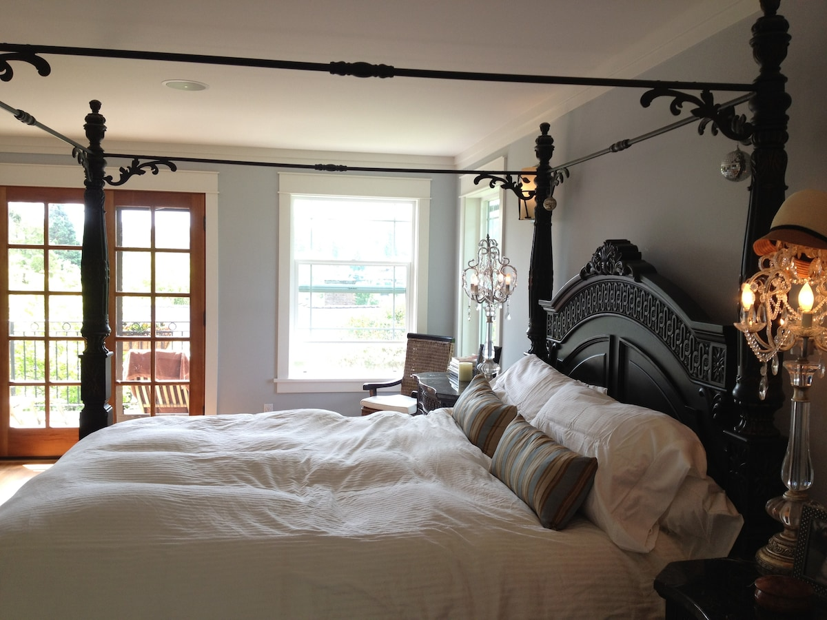 king bed in master. french doors open onto 2nd floor deck with view to canal.
