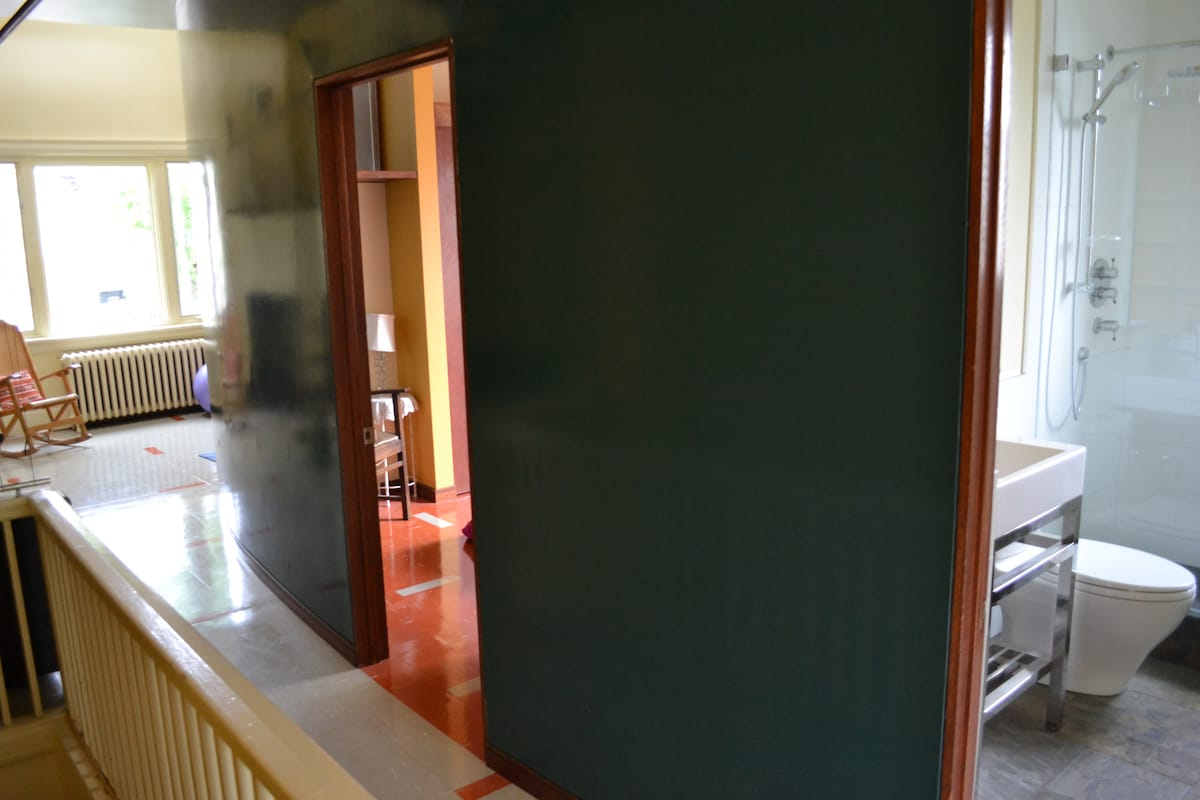 A glimpse of the bathroom and the bedroom from the hall.  All light is natural.