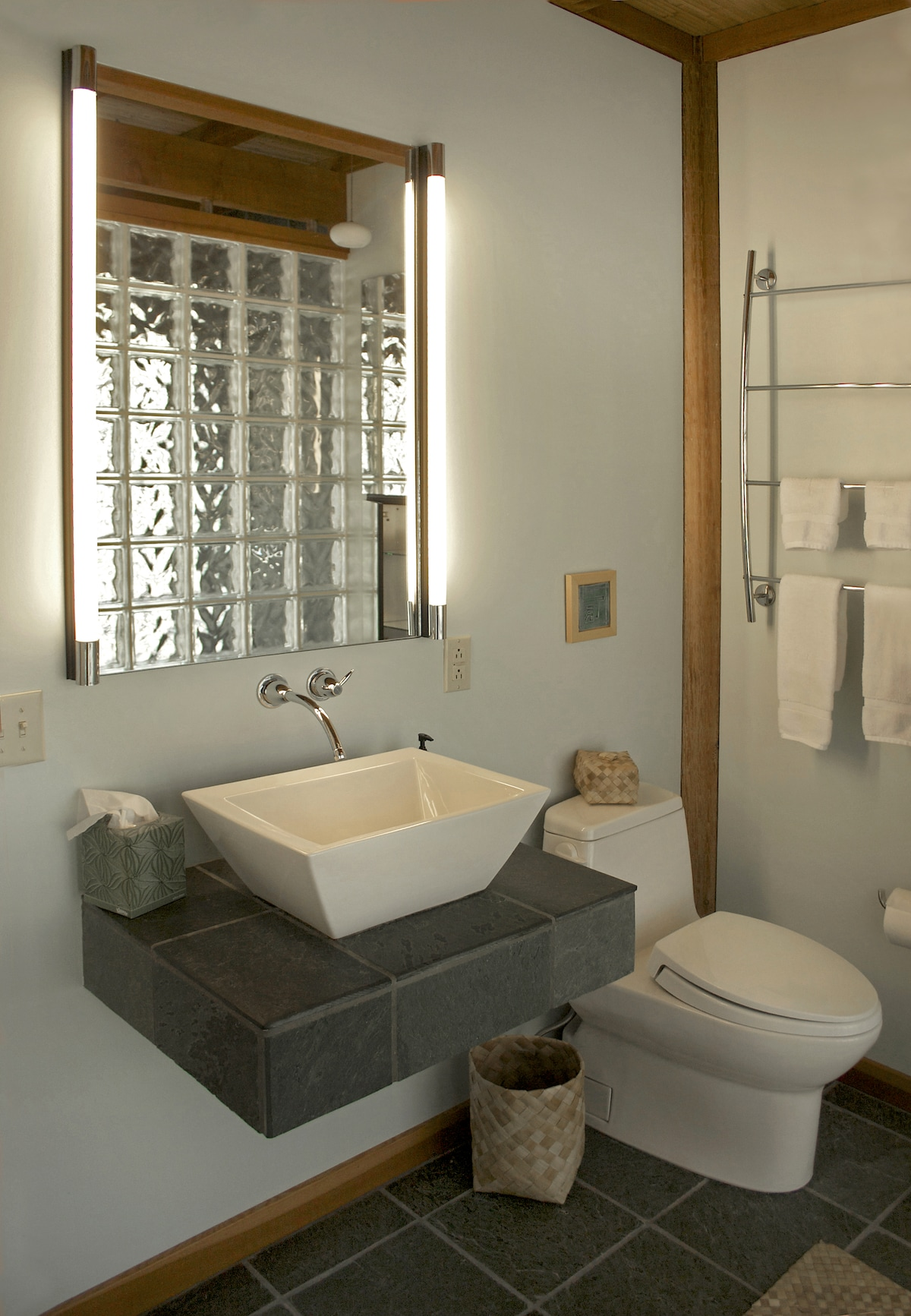 bathroom with slate vanity and vessel sink- glass block shower in reflection