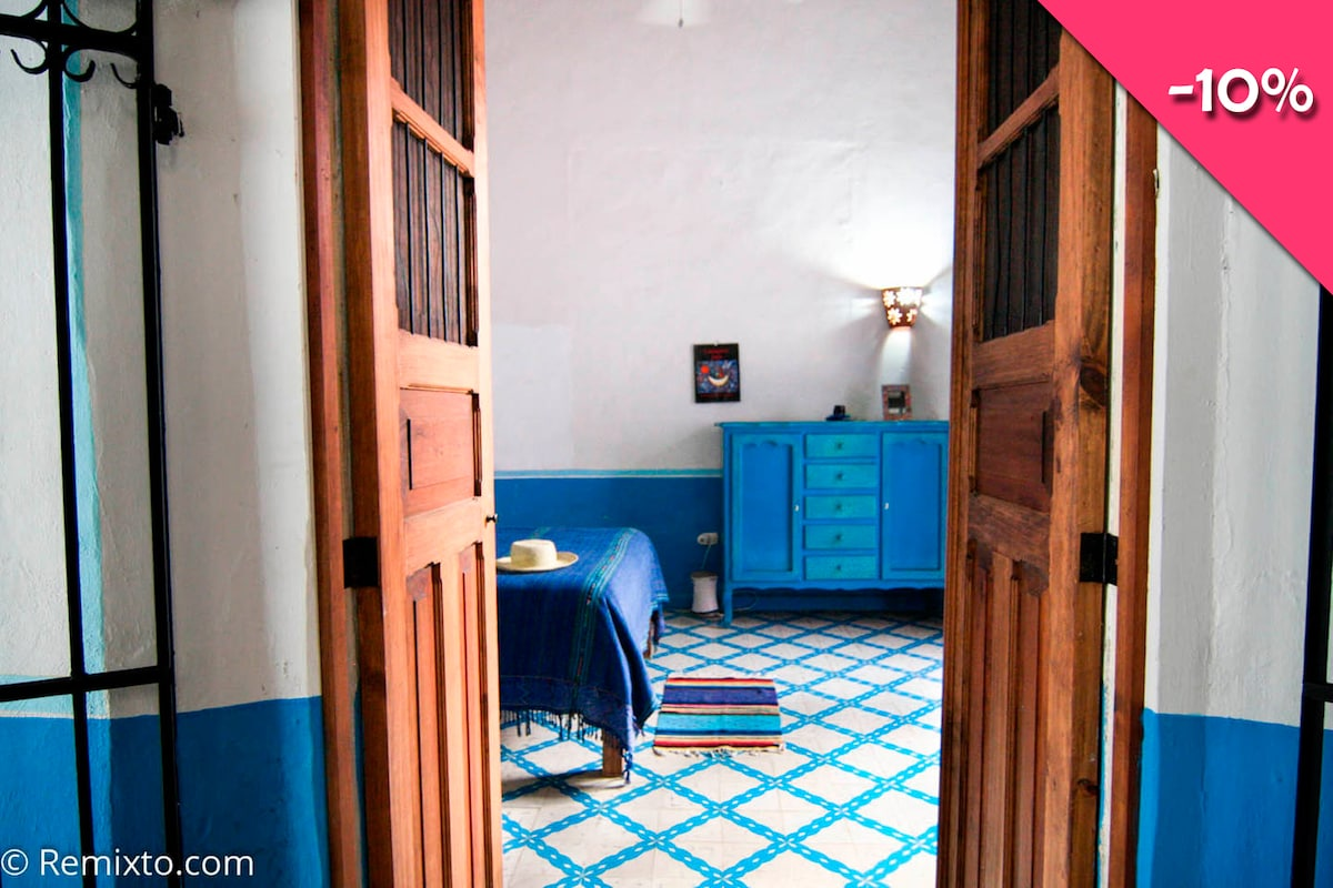 A peek into the guest bedroom with colorful pasta tiles and high original ceilings