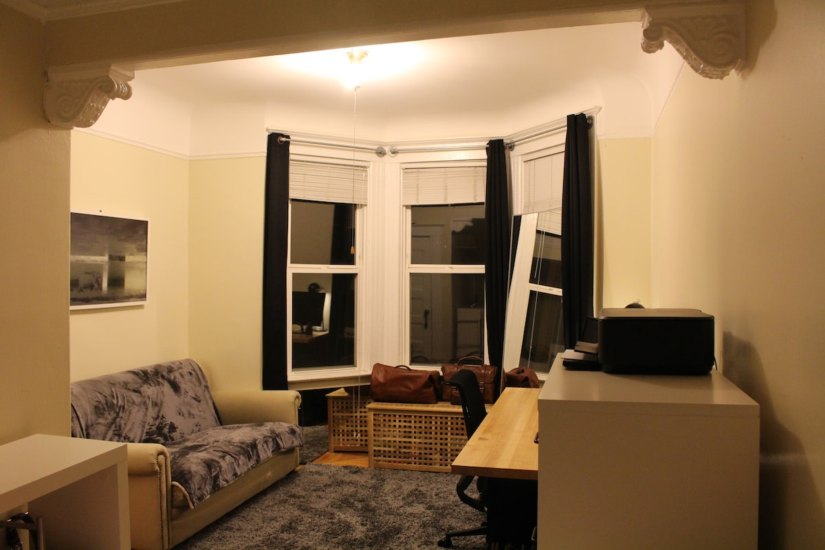The room divided into a space for a bed and space for living/working. There are blackout curtains so you can sleep in, and a couch that is directly across from the large desk.