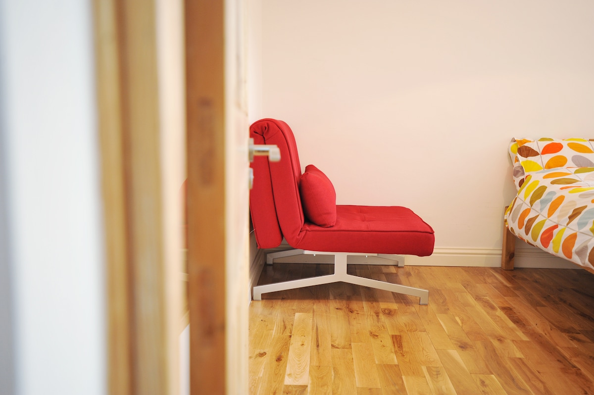 This red chair folds out into a comfortable sofa bed to sleep a 3rd person in this room