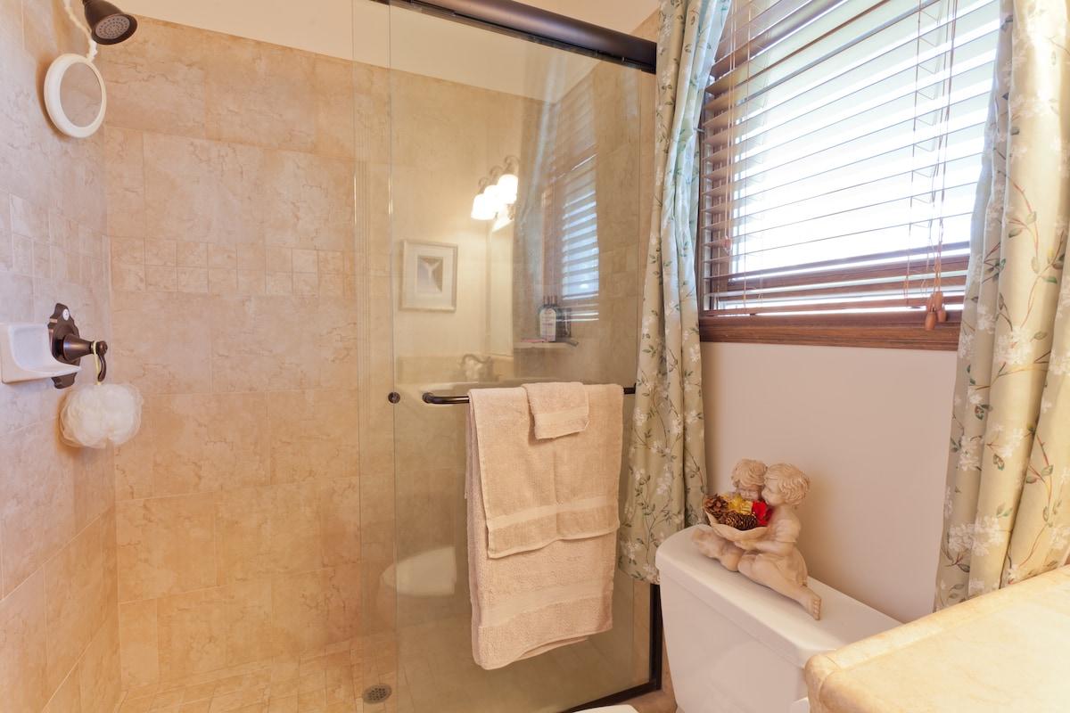 Large tile shower, fresh linens, soap and shampoo.