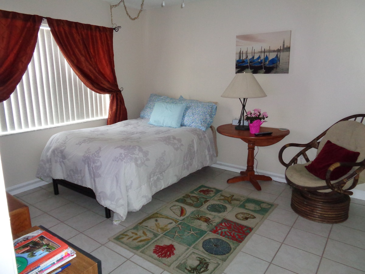 Nice bedroom with full sized real bed,  Bedroom is next to bathroom and front door for easy access. Has table and chair for use with laptop. Free Wifi