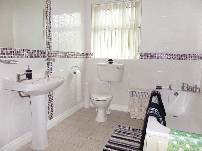 Very spacious fully tiled black and white family bathroom with an  electric shower and  towels supplied FOC