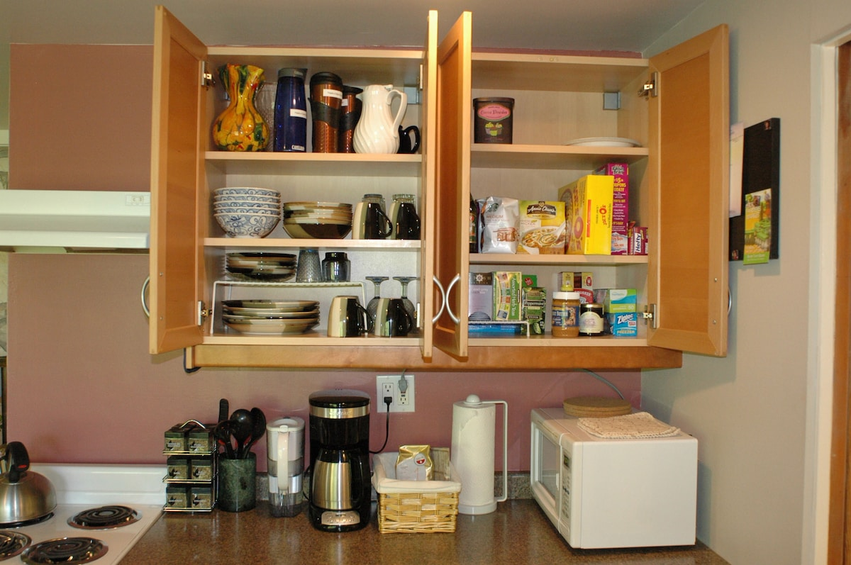 Well-stocked full kitchen and pantry, with stove, fridge, microwave, coffee pot, toaster, sink.