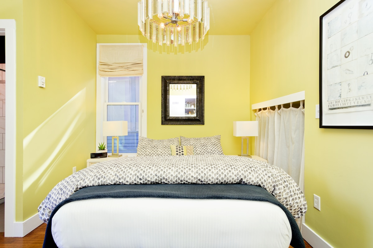 Comfortable queen bed under a disco-style chandelier.