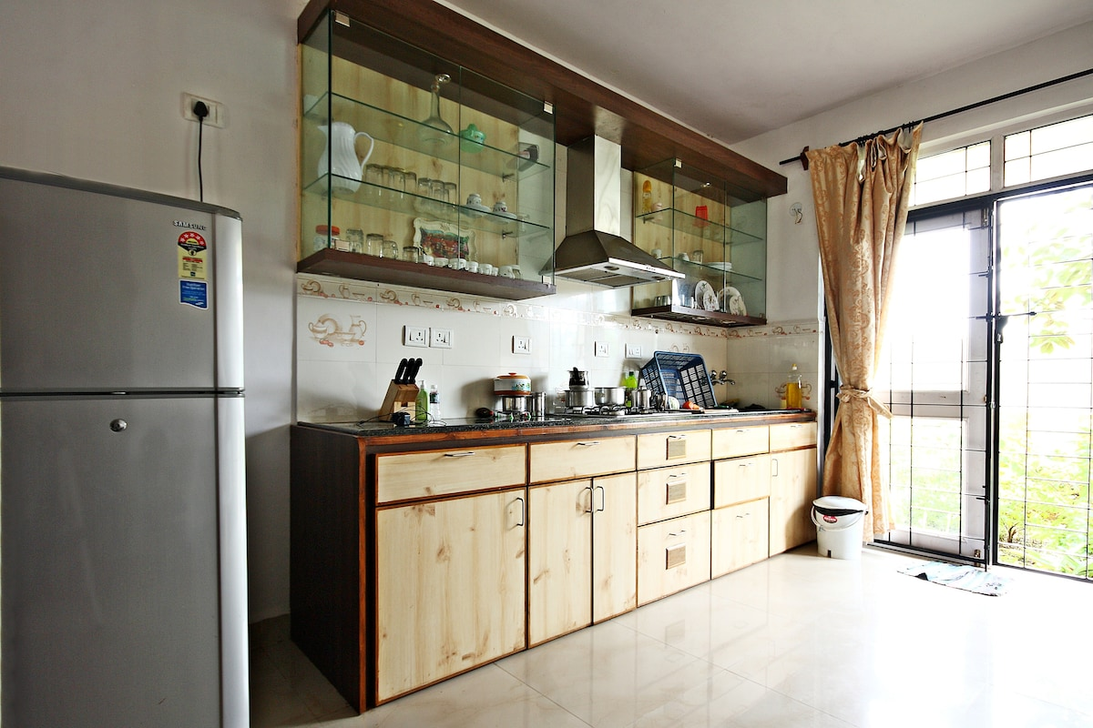 Kitchen with cooking hob, chimney, refrigerator & view to the green fields outside