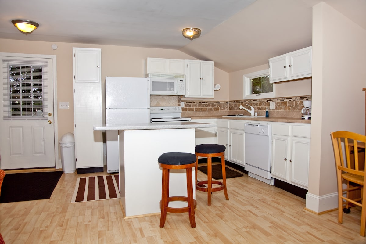 Large kitchen with above stove microwave, icemaker, travertine tile backsplash and more.
