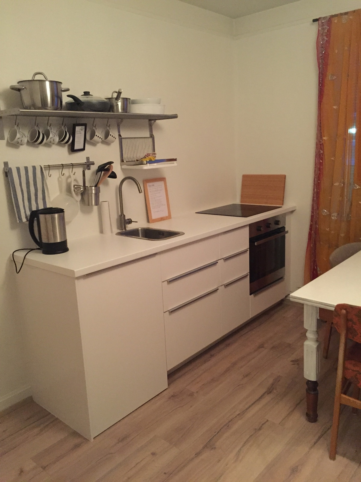 A fully equipt kitchen with a fridge, a stove and an oven.