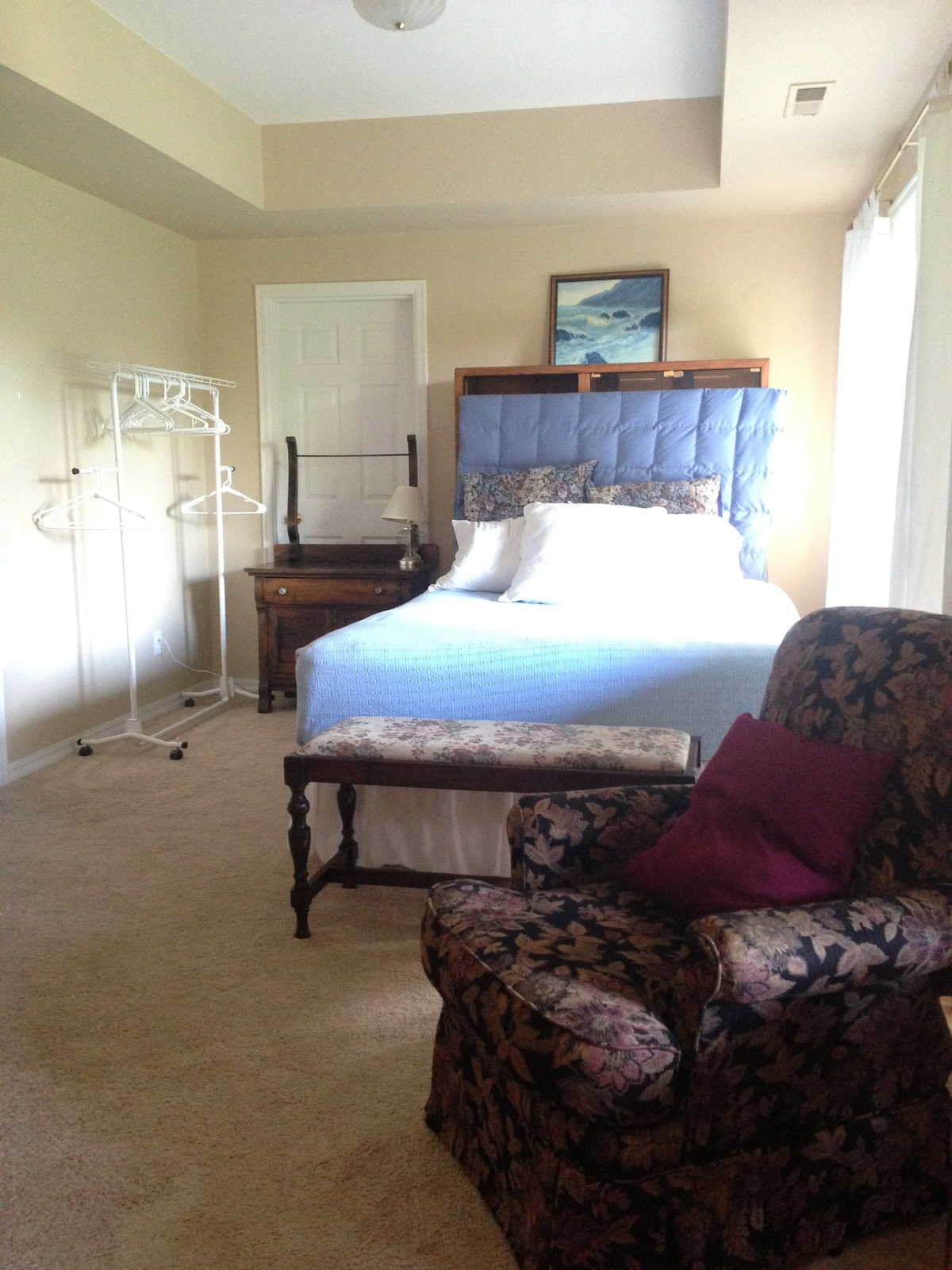 Queen bed with wardrobe rack, dresser and luggage stool.