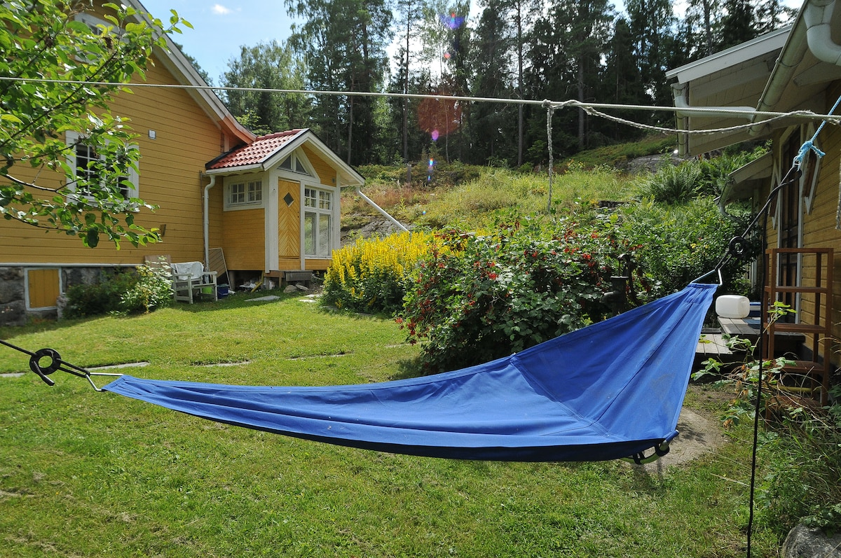 Hammock under the apple tree; bathroom in the background, attached to host´s house only for your use.