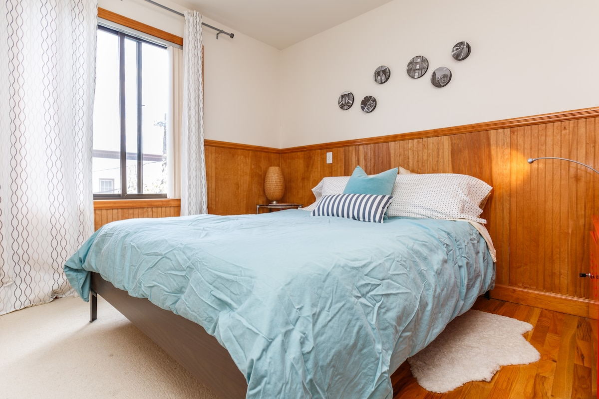 Middle bedroom with queen bed, bedside lamps, large closet