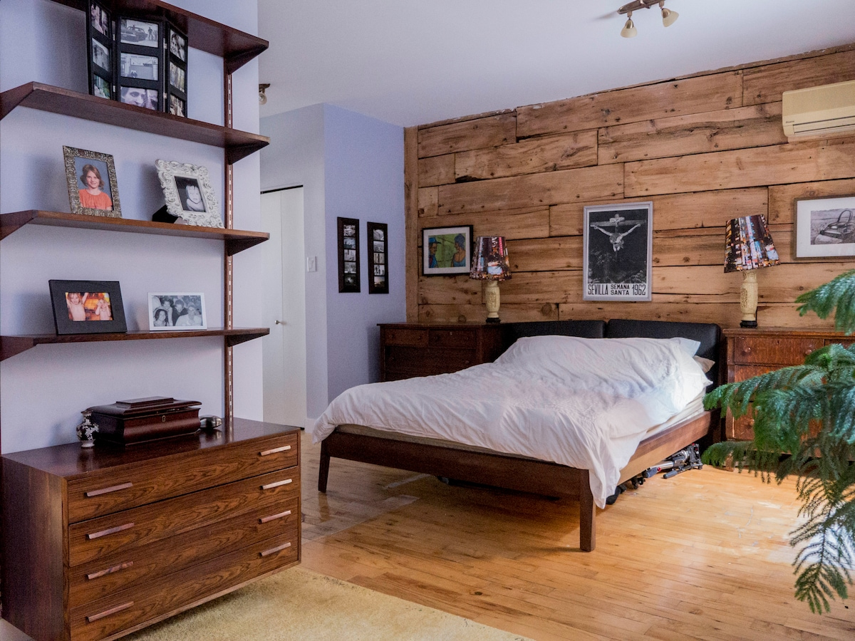 "Master bedroom, with ensuite full bathroom. Very comfortable Queen sized bed with pillow top. Exposed ""Quebec frame"" wood wall."