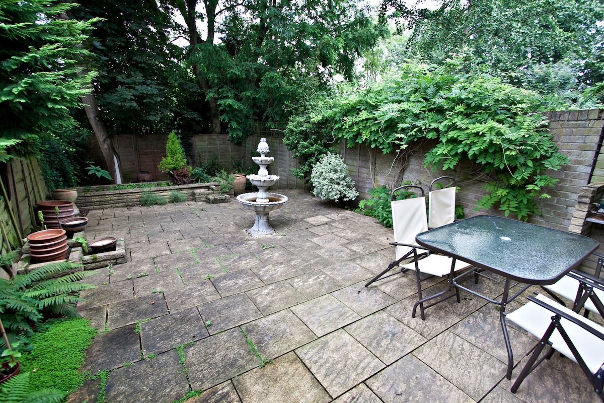 The simple outdoor area includes table and chairs, as well as a brick barbecue.