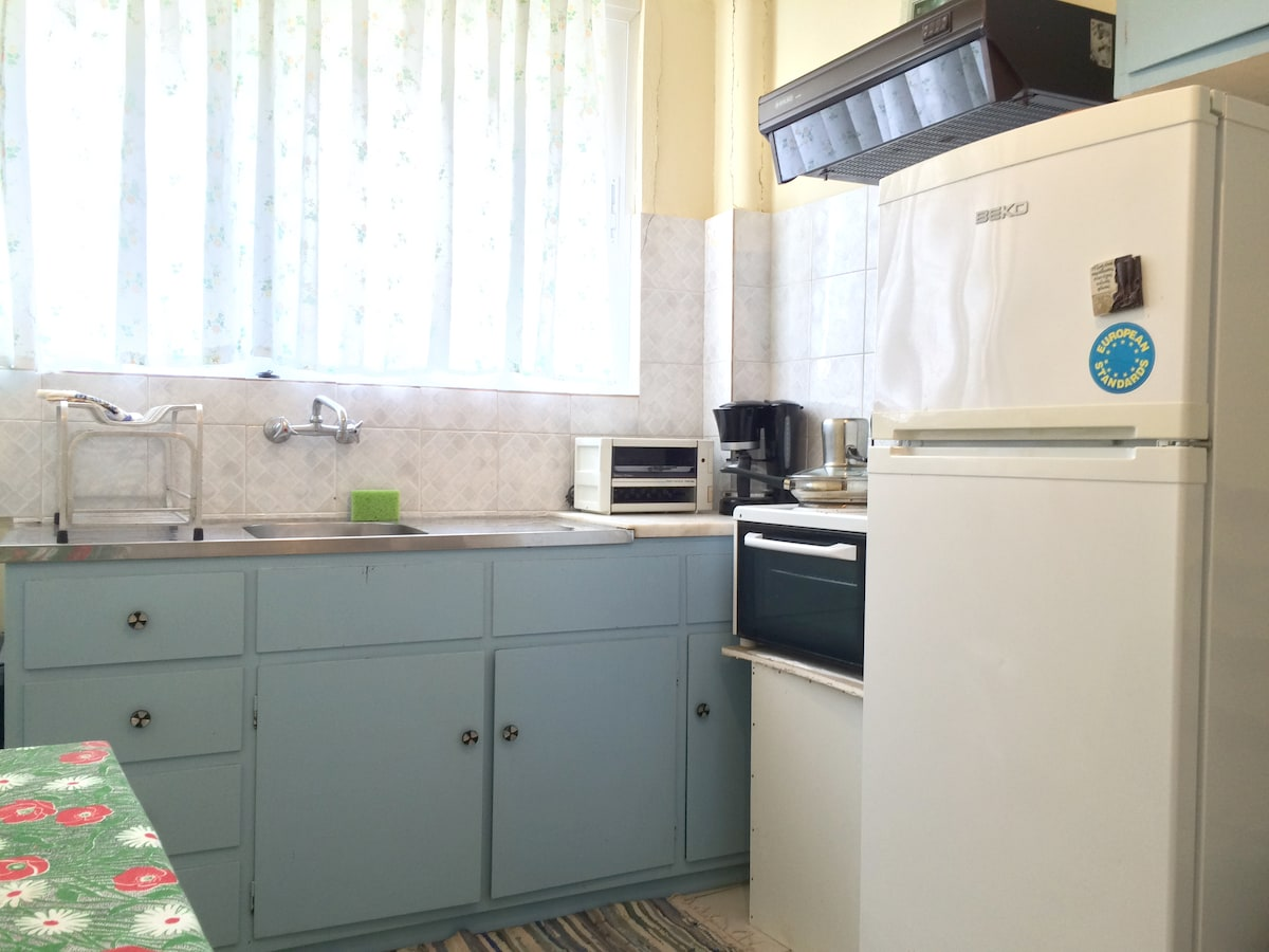 Spacious kitchen with fridge, oven and coffee maker.