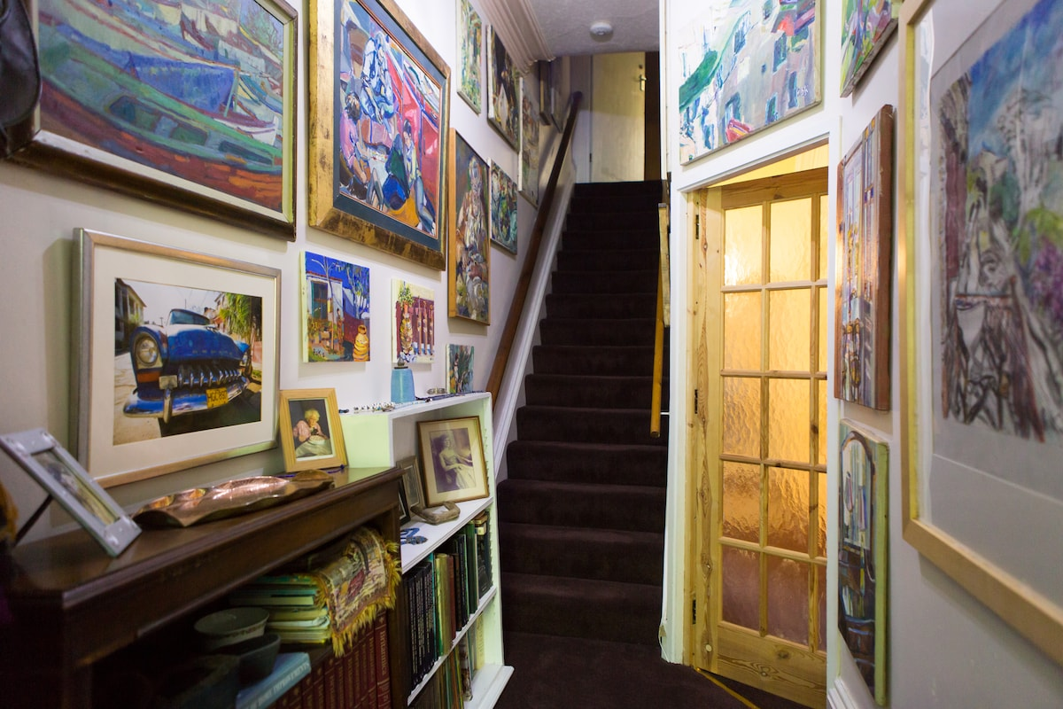 Main entrance hallway filled with my oil paintings and photographs. These stairs lead up to your room.