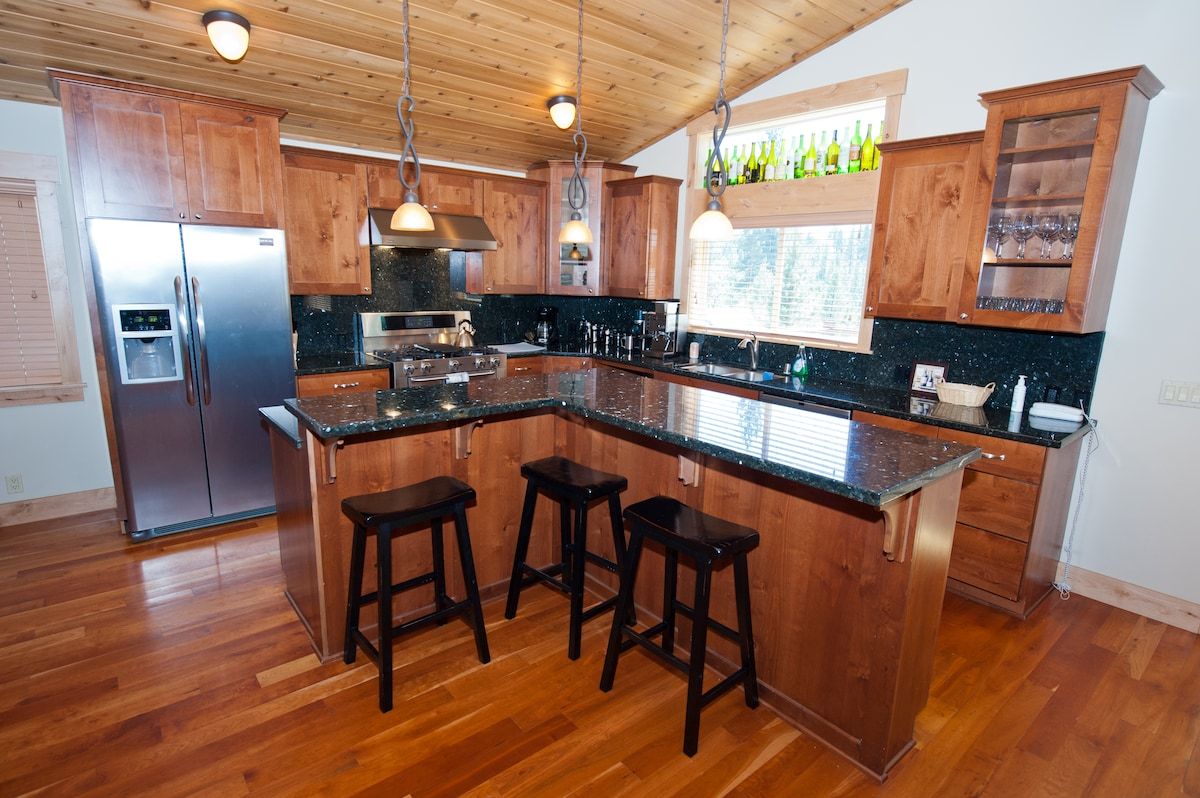 Chef's kitchen with granite counter tops, stainless appliances, and a large island for preparation and dining