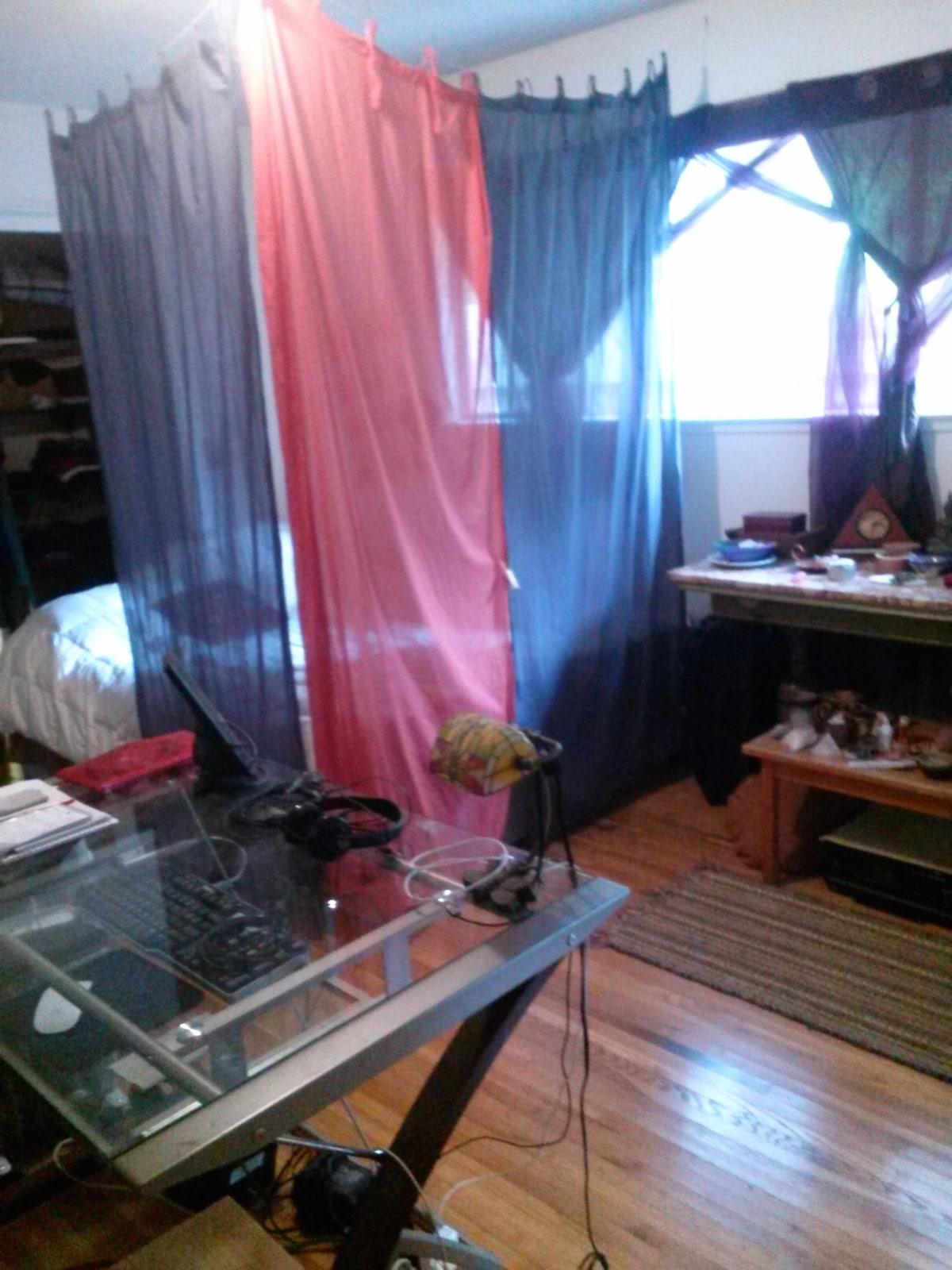 The bedroom... bed, desk, wood floors