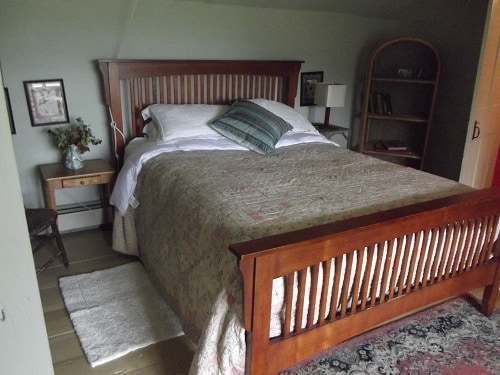 Queeen-sized bed in the Dormer Room faces the view of meadows and Vermont hills