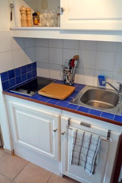 Kitchenette with ceramic heater, chopping board, kitchen utensils complete.