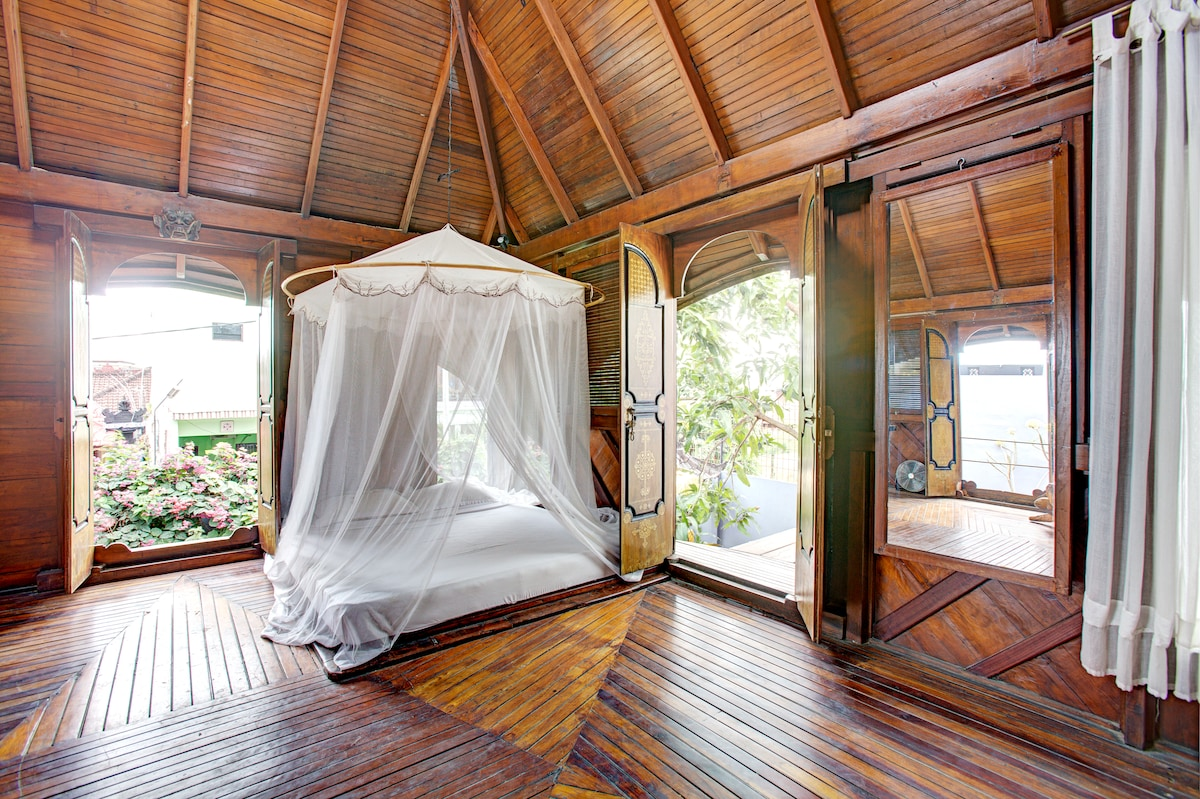 Queen size bed on a low wood/bamboo base. Large doors open in all 4 directions to catch every breeze.
