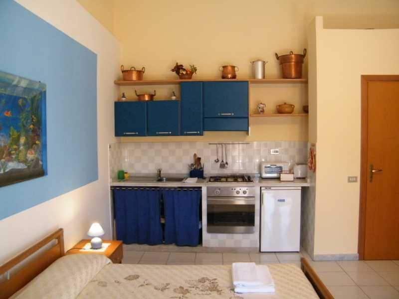 on the right side of the bed there is the kitchen with one, dishes, and some appliance